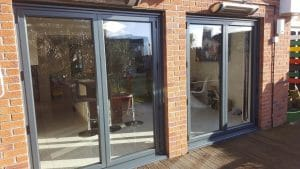 Grey double patio doors leading onto decking - SRJ Windows