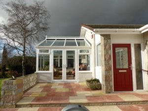 Red composite doors with conservatory in background