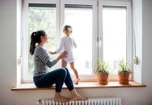Beautiful young mother sitting on window sill with her cute little daughter looking out of window