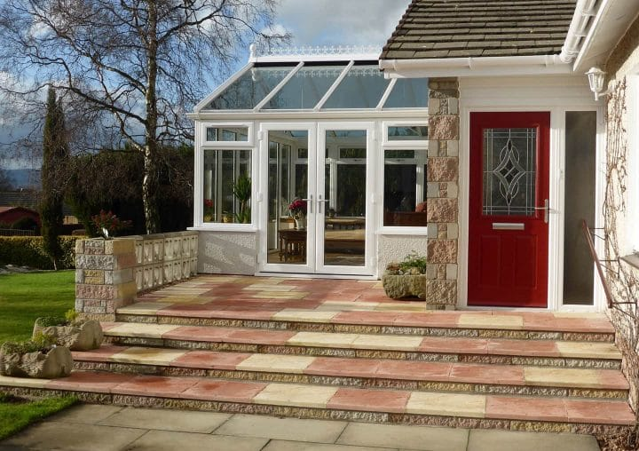 Red composite door with a side conservatory